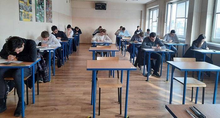 Uczniowie siedzą przy stolikach i piszą na kartkach